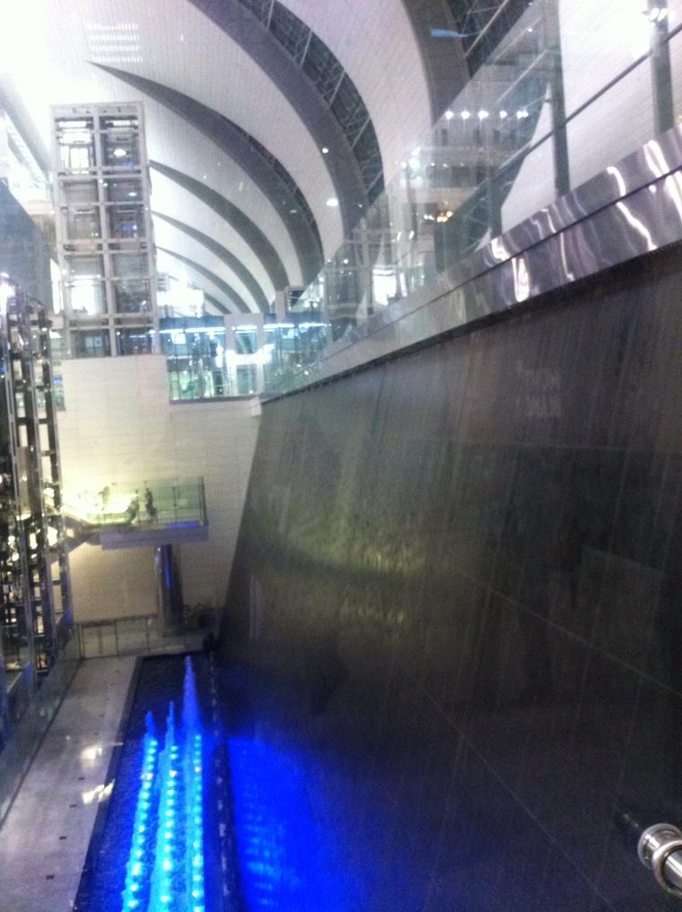Mit eigenen Augen sieht dieser dekorative, riesige Wasserfall im Flughafen von Dubai noch mächtiger aus.